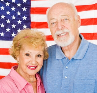 Veteran and his wife in front of flag
