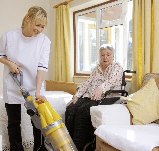 Home health aide vacuuming for senior woman