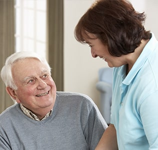 Senior care aide smiling at senior man